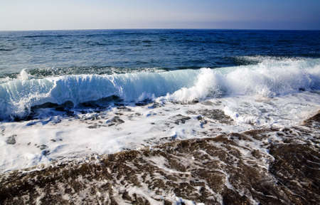 foamy: foamy shore blue waves over the horizon in a clear summer day Stock Photo