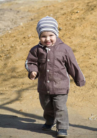 boy is dressed in warm clothes walking on playground photo