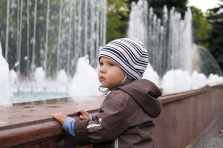 boy is dressed in warm clothes on a walk in a park photo