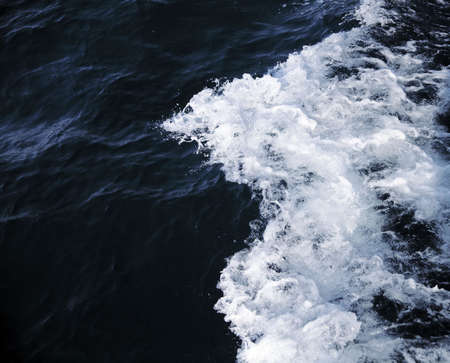 dark sea water with waves and white suds photo