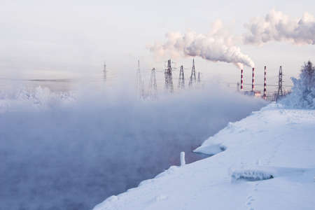 water tower: Winter landscape with steam over the river and factory on a background