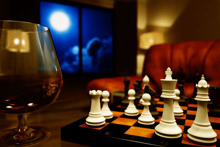 moon chair: Interior with a glass of cognac and chess at night Stock Photo