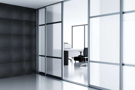 Empty cubicle with laptop on table behind a glass doors in modern office photo