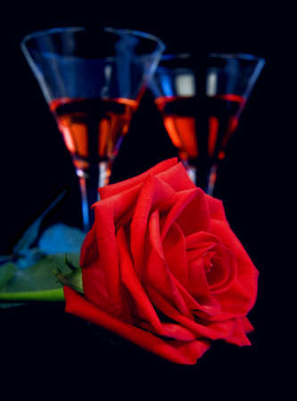 dating and romance: Gentle red rose and liquor in a glasses on a black background