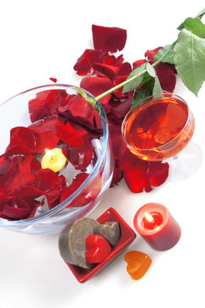 Red rose in an environment of petals and soap and a burning candle on a white background photo