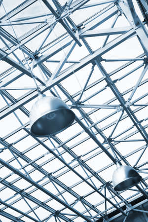 girders: blue toned lamps and metallic girders under glass ceiling of industrial building
