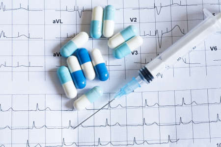 Syringe and tablets on the paper with graph of heart rhythm Stock Photo - 9506867