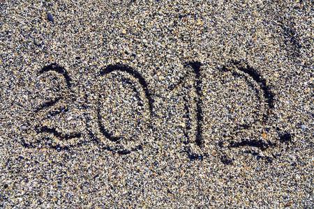 Inscription of year 2012 on sea coast photo