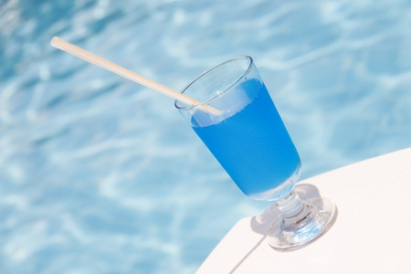 freshening: Freshening cocktail of blue color against water pool Stock Photo