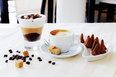 hot coffees: coffee and sweat candies on white table Stock Photo