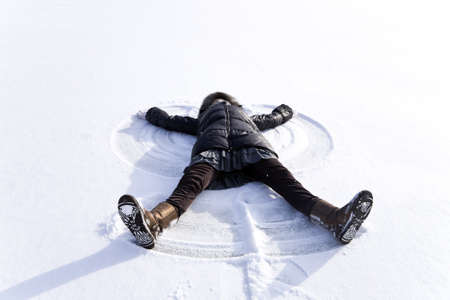 young woman kidding on snow in winter day photo