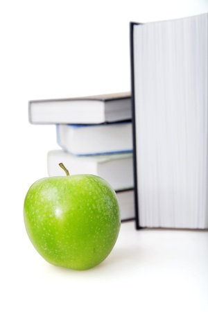 Bright green apple and books on a background