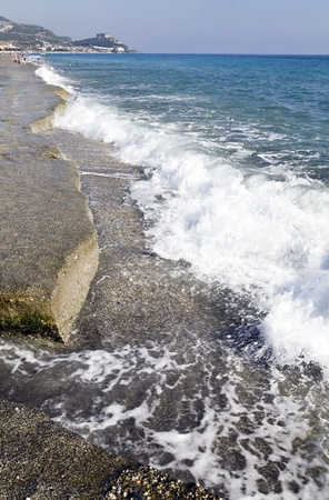 tourist feature: coast from pebble and blue foamy sea waves Stock Photo