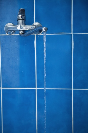 soppy: water tap with flower water against a blue ceramic tile Stock Photo