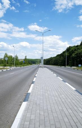 single lane road: asphalt road with a divider for pedestrians Stock Photo