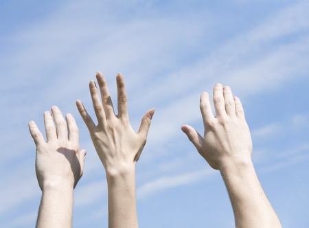 hands are lifted to a blue cloudy sky photo