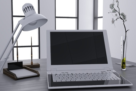 laptop and flower in vase on table in modern cubicle photo