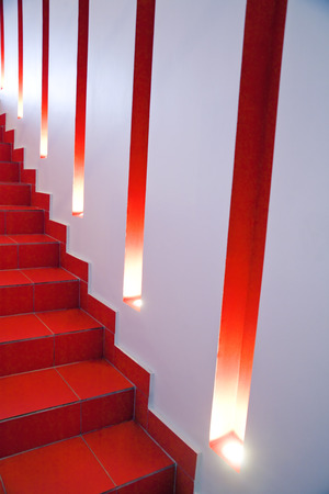 niches: wall of a modern building with lights and niches and red stage