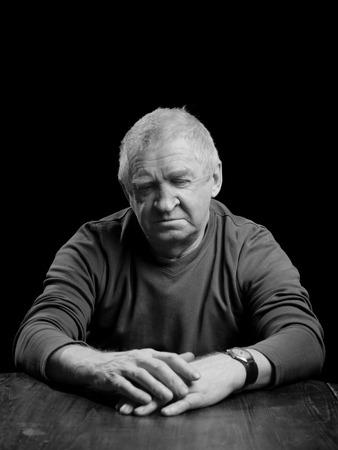 Portrait of a senior man looking very serious, sad or depressed ,studio shot over black.  photo