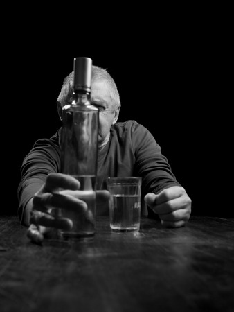 torment: portrait senior man  pouring white alcohol in a glass