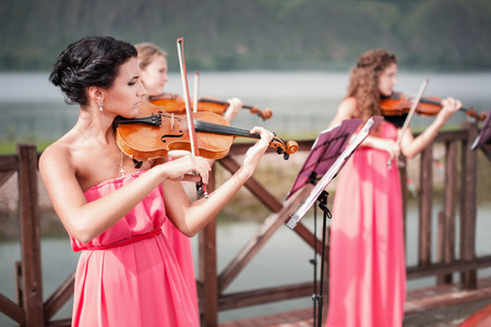 Girls plays violin outdoors near the river photo