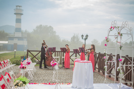 Quartet of classical musicians playing at a wedding outdoors near the river photo
