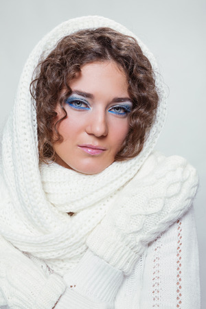 unworried: young curly-haired beauty in a white scarf and mittens Stock Photo