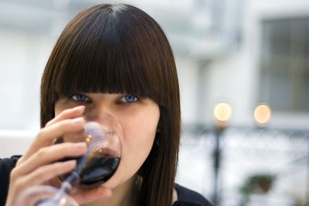 The woman at restaurant drinks wine
