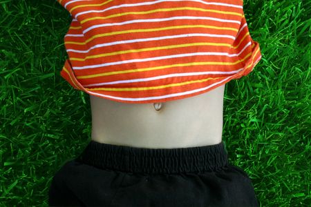 belly button: a childs tummy is shows while he lays in the grass Stock Photo