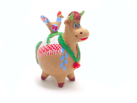 Isolated clay figurines cow with a bird on his back Stock Photo