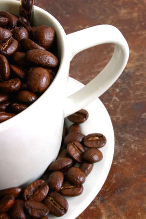 caf: Coffee beans in cup on rich, brown surface
