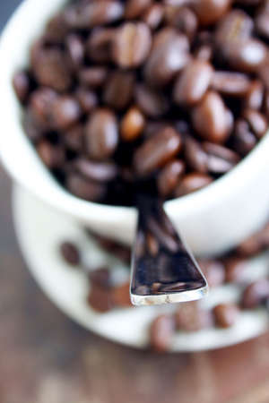 Coffee cup with spoon and beans; Focus on tip of spoon