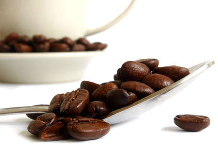 Coffee beans on spoon with background cup Stock Photo