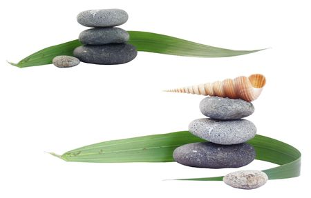 eastern philosophy: Pebble stacks with palm leaf and seashell; isolated over white