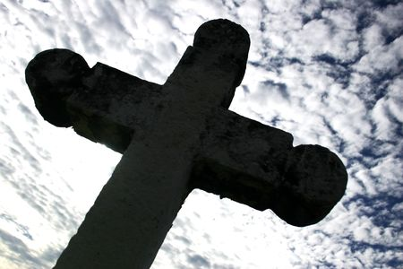 Gothic crucifix silhouette with dramitic sky backdrop photo