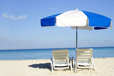 loungers: Umbrella and loungers on the beach Stock Photo