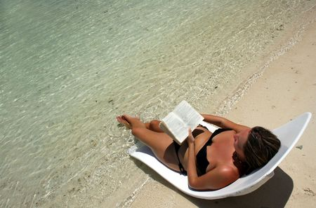 Girl on lounger reading by tropical sea