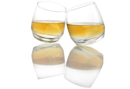 hard love: Two touching whiskey glasses with reflections Stock Photo