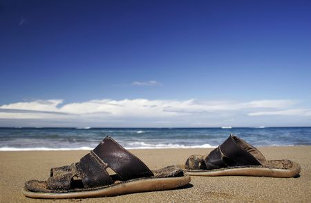 Leather sandals on golden beach Stock Photo