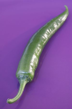 Green chili pepper on purple plate photo