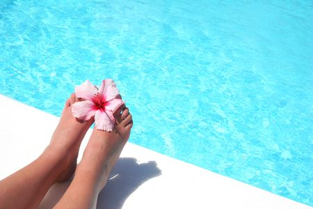 Womens feet by pool with flower photo