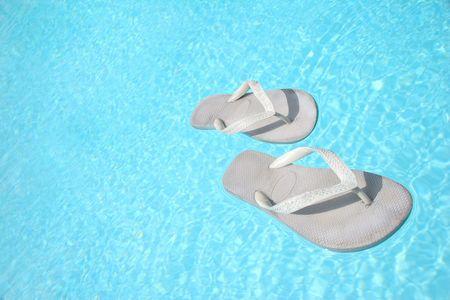 feat: Flip-flops flotando en la piscina de color azul  Foto de archivo