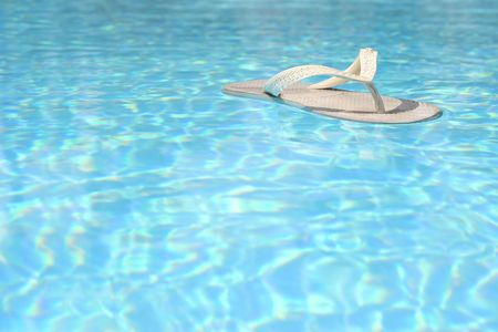 informal clothes: White flip flop floating in blue pool Stock Photo