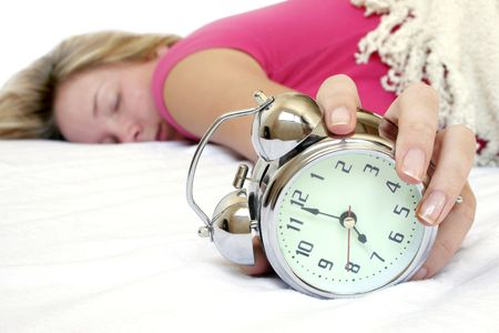 early morning: Woman and alarm clock in bed Stock Photo