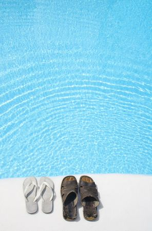 Two pairs of shoes by a bright swimming pool photo