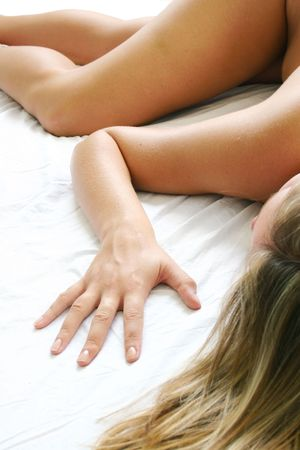 footcare:  woman lying on a white bed