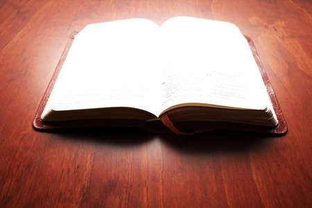 Bible with bright light on the open pages as it were glowing photo