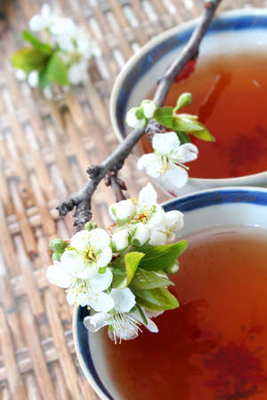 18th: Tea in antique Chinese Porcelain cups (genuine 18th Century) and peach blossom on wicket table Stock Photo