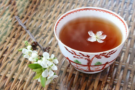 18th: Tea and blossom; tea in 18th Century chinese porcelain bowl Stock Photo