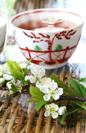 assam tea: Tea and blossom on rattan table Stock Photo